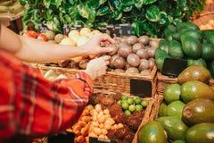 Barnpar i livsmedelsbutik De når handen till exotiskt mål eller mat Folket trycker på det Klipp sikten arkivfoton