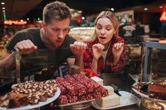 Barnpar i livsmedelsbutik Hungrig man- och kvinnablick på sötsaker på hylla med att förbluffa sikt De önskar att äta det arkivbilder