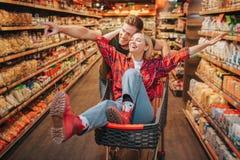 Barnpar i livsmedelsbutik Kvinnan sitter i spårvagn och att ha gyckel Manställning bak och punkt på hylla med produkter royaltyfria bilder