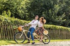 Barnpar med cykeltandemcykeln parkerar in Ungdomarhåller hattar i deras händer och leende På baksidan av trädstaketet royaltyfri bild