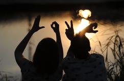 Barnpar på en solnedgång Fotografering för Bildbyråer