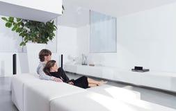 Barnpar på hållande ögonen på TV för soffa Arkivfoto