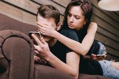 Barnpar på soffan med mobiltelefonen Royaltyfri Bild
