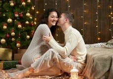 Barnpar sitter på golv i mörk träinre med ljus Romantisk afton och förälskelsebegrepp Ferie för nytt år Julligh arkivfoton