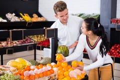 Barnpar som avgör på frukter shoppar in Arkivfoto