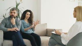 Barnpar som besöker det yrkesmässiga psykologkontoret Lockig kvinna som argumenterar och talar angrily om hennes pojkvän till stock video