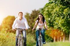 Barnpar som cyklar med cykeln i sommar Arkivfoto