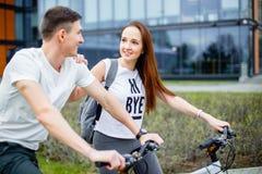Barnpar som går för en cykel, rider på en solig dag i staden royaltyfria bilder