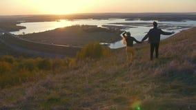 Barnpar som går i händer för ett fältinnehav på solnedgången arkivfilmer