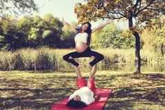 Barnpar som gör acroyoga Gravid kvinna ovanför hans le för man fotografering för bildbyråer