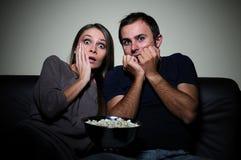 Barnpar som håller ögonen på läskig film på tv Royaltyfri Foto