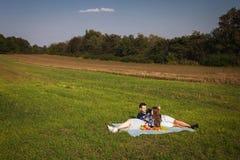 Barnpar som har picknicken på gräsmattan Arkivfoton