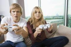 Barnpar som hemma spelar videospelet i vardagsrum Royaltyfri Bild