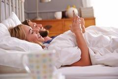 Barnpar som ligger i säng genom att använda mobiltelefoner arkivbild