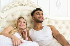 Barnpar som ligger i säng, latinamerikansk man för lyckligt leende och kvinnan som upp till ser kopieringsutrymme Fotografering för Bildbyråer