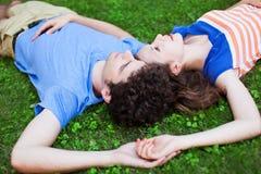 Barnpar som ligger på gräs Fotografering för Bildbyråer