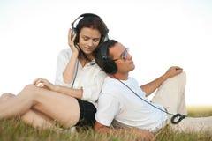 Barnpar som lyssnar till musik Arkivfoton