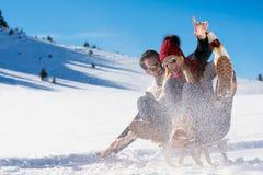 Barnpar som Sledding och tycker om på Sunny Winter Day Arkivbild