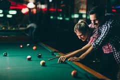 Barnpar som spelar snooker tillsammans i stång Royaltyfri Foto