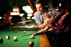 Barnpar som spelar snooker tillsammans i stång Royaltyfria Foton