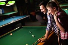 Barnpar som spelar snooker tillsammans i stång Arkivfoto