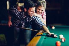 Barnpar som spelar snooker tillsammans i stång Royaltyfri Bild