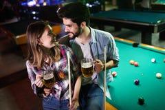 Barnpar som spelar snooker tillsammans i st?ng arkivbilder