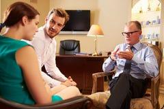 Barnpar som talar till den manliga rådgivaren royaltyfri bild
