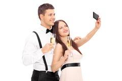 Barnpar som tar selfie med mobiltelefonen Arkivbild