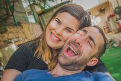 Barnpar som tillsammans tycker om i trädgården De är le, skratta och göra roliga framsidor tillsammans Arkivfoton