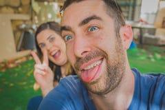 Barnpar som tillsammans tycker om i trädgården De är le, skratta och göra roliga framsidor tillsammans Royaltyfria Bilder