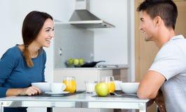 Barnpar som tycker om frukosten i köket Arkivfoton