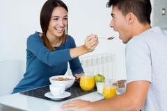 Barnpar som tycker om frukosten i köket Arkivfoto