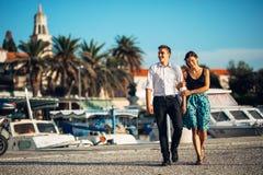 Barnpar som tycker om semestertid Pojkvännen och flickvännen som har en romantiker, promenerar kusten i en sjösidastad royaltyfria foton
