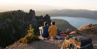 Barnpar som tycker om solnedgång över berg royaltyfria bilder