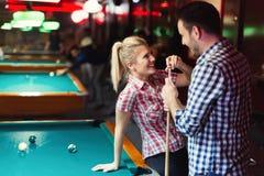 Barnpar som tycker om spela snooker på datum Arkivfoton