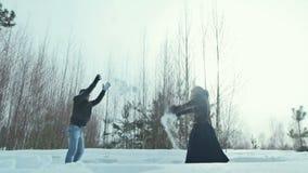 Barnpar som utomhus spelar i snön lager videofilmer