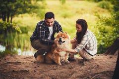 Barnpar utomhus med hunden Arkivfoto