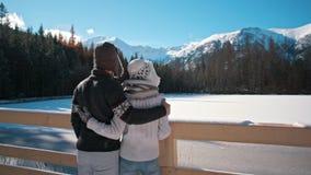 Barnparet är den stående near berg sjön i vintern som beundrar Landskape stock video