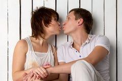Barnparet är kyssande nära den vita träväggen royaltyfria bilder