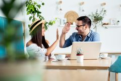 Barnparet arbetar i kafé på bärbara datorn och att le - Bild arkivfoton