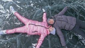 Barnparet har gyckel under vinter att gå mot bakgrund av is av den djupfrysta sjön Vänlögn på klar is med sprickor lager videofilmer