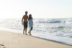 Barnparet tycker om att gå på en disig strand på skymning arkivfoto