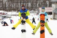 barnparsnowboarders jublar och är glade Royaltyfri Bild
