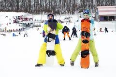 barnparsnowboarders jublar och är glade Arkivfoton
