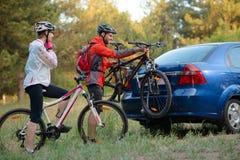 BarnparUnmounting mountainbiken från cykelkuggen på bilen Affärsföretag- och familjloppbegrepp Royaltyfria Bilder