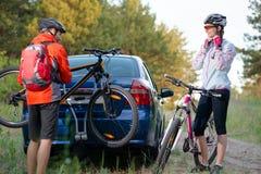 BarnparUnmounting mountainbiken från cykelkuggen på bilen Affärsföretag- och familjloppbegrepp Royaltyfri Foto