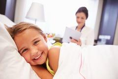 Barnpatient för doktor som Making Notes On använder den Digital minnestavlan royaltyfria bilder