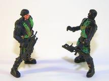 Barnplast-soldater, två diagram av banditer i form av ett vapen Bilden togs i närbild royaltyfri fotografi