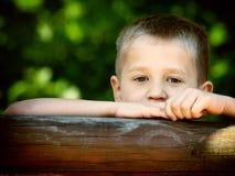Barnpojke eller unge som spelar på lekplats Arkivbild